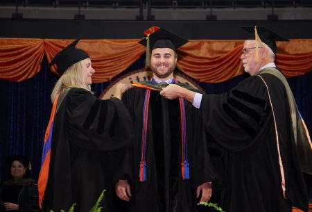Stacey Curtis, Pharm.D., and Sven Normann hood a new graduate at commencement.
