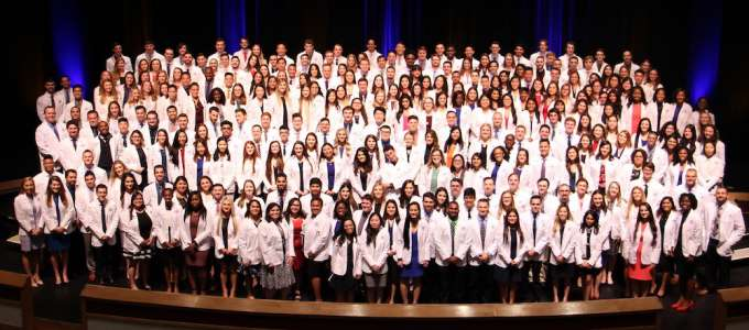 Students pose after receiving white coats
